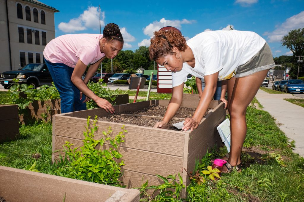 Chloe and a youth member plant seeds in snack beds.