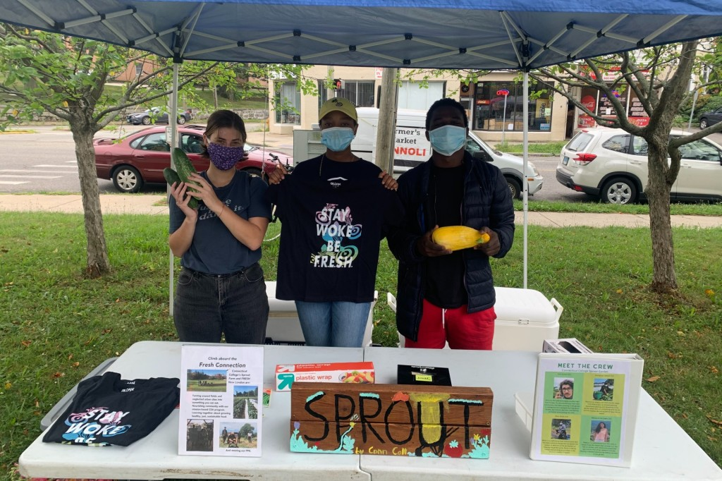 Grace, a FRESH youth member and a Connecticut College student hold vegetables and FRESH merch at our Farmer's Market table, wearing masks for safety.